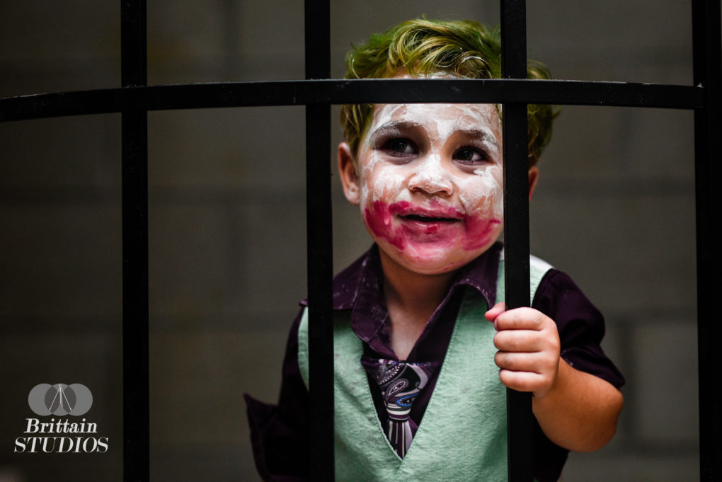 """October 25th – One of the photos we definitely wanted to do this year was """"The Joker,"""" and we were looking to resemble Heath Ledger's version from """"The Dark Knight."""" We debated visiting an abandoned prison where you can go into the cells, but it seemed to make more sense to create our own. We purchased an iron trellis from Lowe's and brought it down to our basement. We have a small unfinished storage room with a cinder block wall, so we set it up in the entryway. Caroline and Charlie played with some toys in the room while I was just outside pointing my camera at the door. When he eventually noticed me and walked up to the bars, I snapped a few shots and was lucky enough to immediately get an evil smile out of him."""