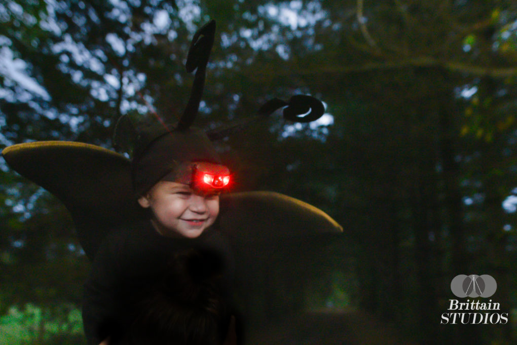 October 23rd – On one of my many trips to Goodwill over the last several months, I found a pair of giant foam elf ears meant to stick out of the side windows of a car. The cogs in my head started turning, and I realized if I spray-painted them black that they would be fantastic Mothman wings. I ordered a headlamp with a red light and found some fake butterfly antennae in the Halloween section of Target. We had had our eyes on a path in Brick near the cabin where we did the Evil Dead shoot. We felt that it would be the perfect creepy background for the shot. We went there just before dusk a few nights ago, and Caroline put Charlie on her shoulders and bounced him for a minute or two while I took the photos. Despite a few strange looks from a midget football team that was practicing in a nearby field, we were in and out in five minutes. Only a few more shoots to go before we can celebrate the end of October!