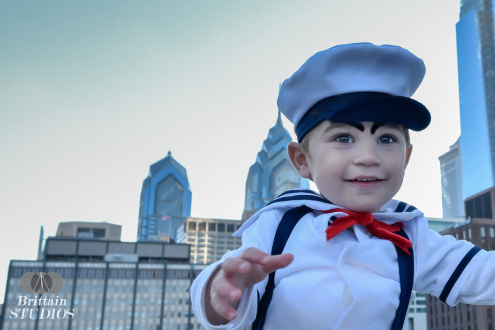 October 24th – We had a sailor outfit that we had purchased last year, so it seemed economical to make a few adjustments and dress Charlie as the Stay Puft Marshmallow Man from Ghostbusters. We took a day trip to Philadelphia yesterday and got a few of our last remaining photos out of the way. Since the Marshmallow Man most famously walks through New York City, we were looking to have a similar skyline in the background without having to travel into Manhattan. Caroline suggested we go to the top of a parking garage, so we went 14 floors up and put on Charlie's costume. At the last second I realized we were missing the red handkerchief, but what we did have was a Winnie the Pooh costume I had found at Goodwill and a sharp pair of scissors. I apologized to Winnie as we cut up his shirt to make the handkerchief, but it was indeed necessary to round out the costume.