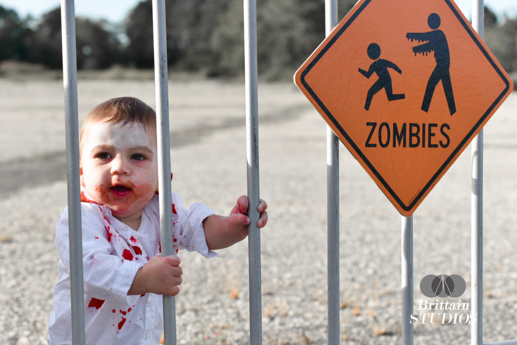 October 10th – In honor of the Asbury Park Zombie Walk today, we're posting The Zombie picture. Taken a few weeks ago, Charlie was just gaining the ability to stand on his own. My sister-in-law, Laura, and I went to an abandoned parking lot I had had my eye on for a while. She stood him up and waited just out of frame, and he held on tight and made the best zombie pose I could have ever hoped for. I had covered his shirt and mouth with red corn syrup to complete the look and hung a zombie sign on the fence as an extra accessory to the photo.
