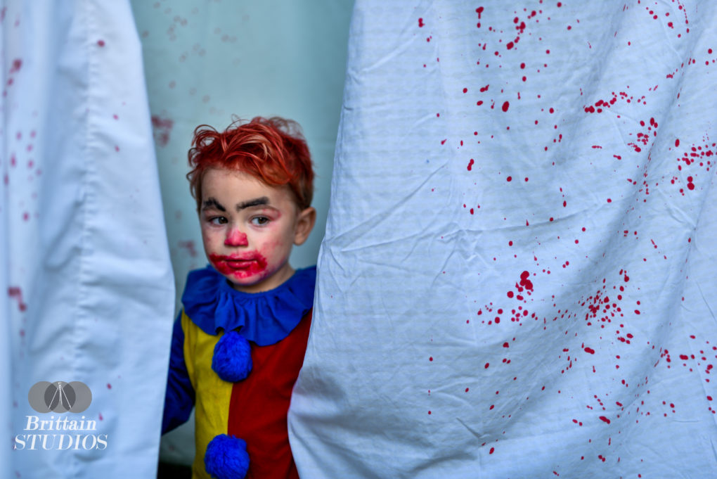 """October 8th – Last year we took a Mischievous Clown photo, but this year we were hoping to go a bit darker with our homage to the movie """"It."""" We ordered Charlie the closest clown costume we could find to the 1990 TV movie. I bought some sheets from Goodwill to recreate the scene of Pennywise walking through the hanging laundry in the backyard. A little lipstick, a little spray blood, and you've got yourself a baby IT."""