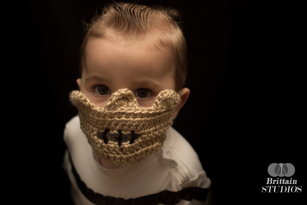 """October 27th – A word of advice if you ever need to dress your seven-month old up as the most popular cannibal in the world: a pacifier will solve all of your problems. We love """"The Silence of the Lambs,"""" but we didn't think there was any way Charlie would be interested in wearing a Hannibal Lecter mask. We figured it was worth a shot, and we asked Caroline's sister, Laura, to crochet one. I'm not sure what I expected, but she totally nailed it. We were thoroughly impressed with the look of it, so we decided to give it a shot. We put Charlie in a long-sleeved white turtleneck, and I put a strip of black electrical tape across the front to look like one of the straps of Lecter's harness . We draped a black tarp behind him as a back-drop. Before we put the mask on his face, I gave him a small pacifier, and he didn't have a care in the world when we put it on. I shot from a few different angles for about a minute, and we were immediately satisfied with the result."""