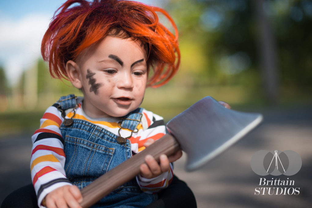 """October 9th – From the very beginning, we knew we had to dress Charlie up as Chucky from the classic 80's movie """"Child's Play."""" Over the course of a few weeks, we were able to find suspenders and an 80's-looking striped shirt to match. I ordered him an orange wig, and we traveled to the park the first sunny day after it arrived. I received a few funny looks from some power-walkers as I sat Charlie in a seat and shot away. He investigated the plastic hatchet in his hands for a few minutes, and his evil grin tells me he's quite pleased with his new toy in this shot."""